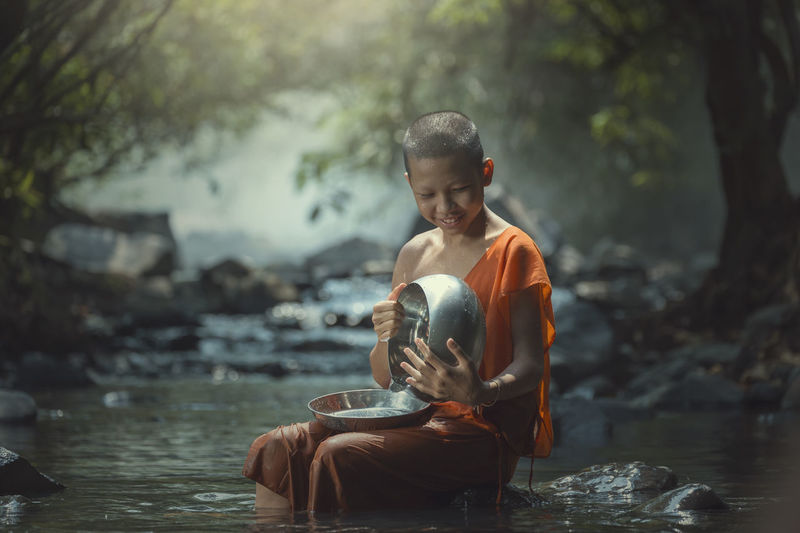 Smiling Monk Holding Bowl And Plate While Sitting On Rock Amidst Stream