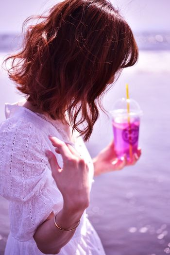 Side view of woman holding drink while standing against sea
