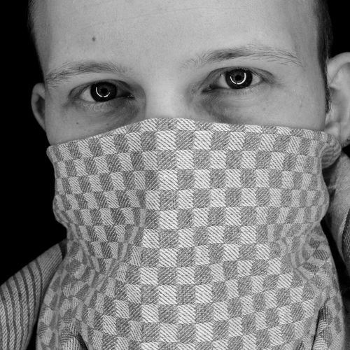 Close-up portrait of man with dish towel over face