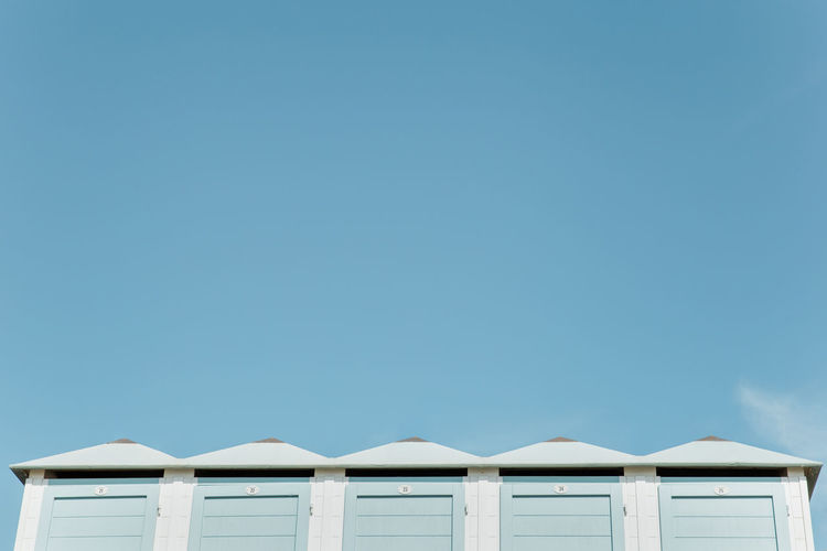 Low angle view of beach huts against clear blue sky