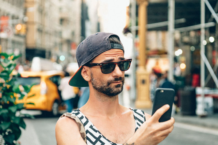Man taking selfie through smart phone in city