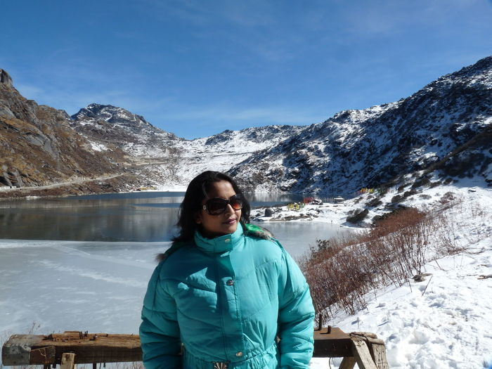 Close-up of woman standing by lake standing against lake during winter