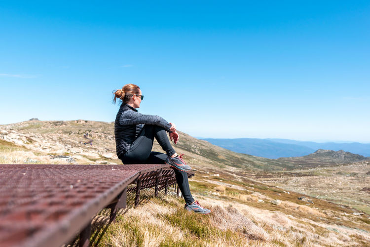 Man sitting on mountain against blue sky