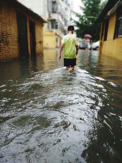 Rear view of boy walking in water amidst buildings