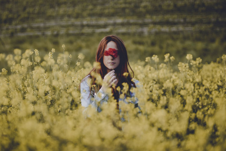 Portrait of beautiful woman with flower amidst oilseed rape field