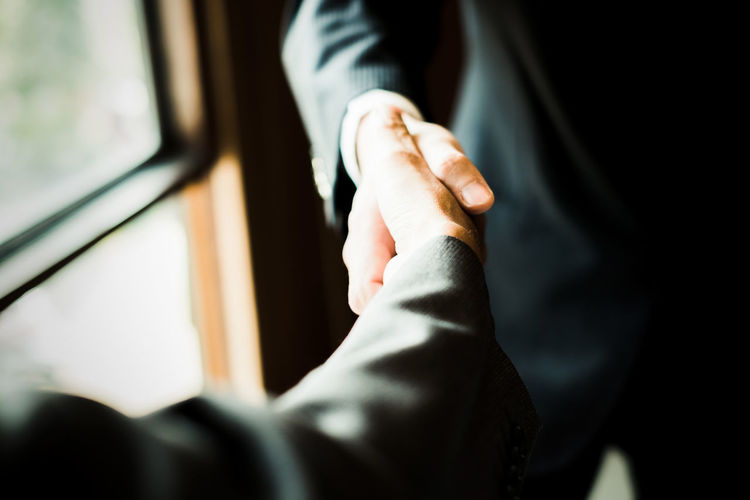 Close-Up Of Businessmen Shaking Hands At Office