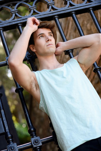 Low Angle View Of Thoughtful Young Man Standing Against Gate