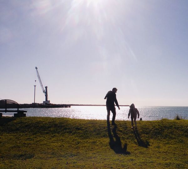 Father and son playing by sea against sky during sunny day