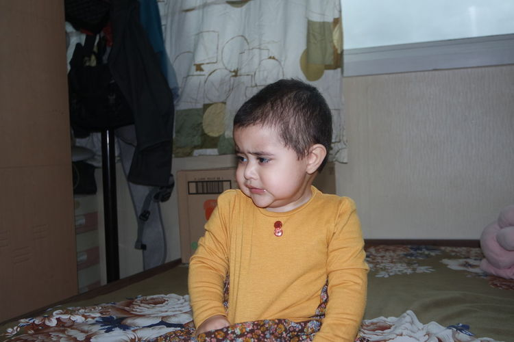 Cute boy sitting on table at home
