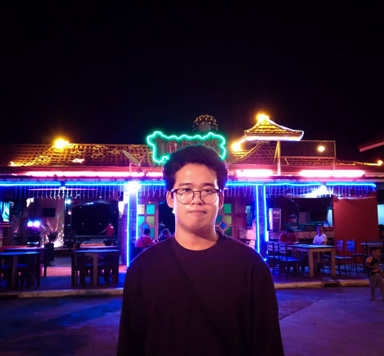 Portrait of young man standing against illuminated lights at night