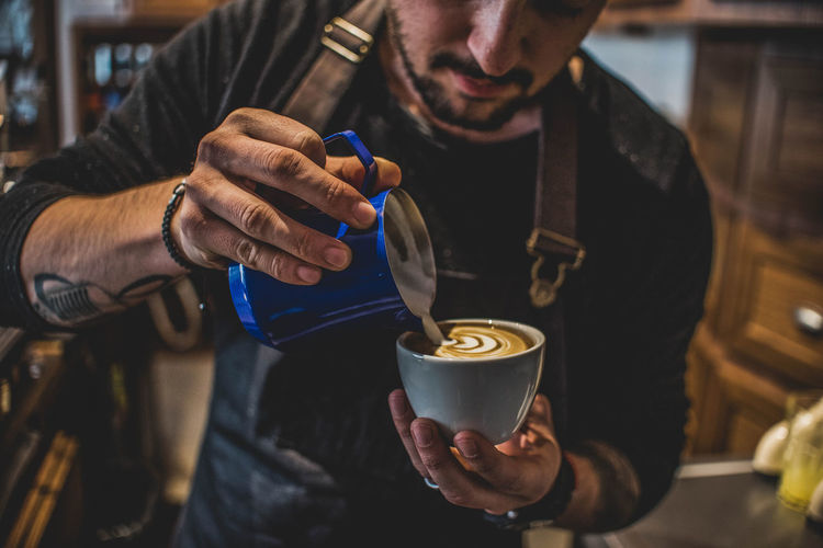 Midsection of man holding coffee at cafe