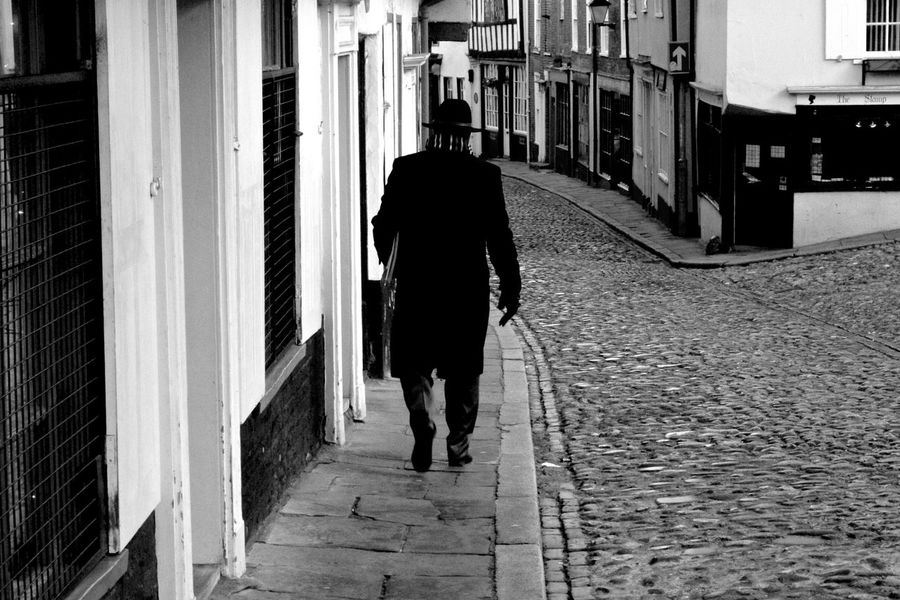 The spy Rear View Walking Full Length One Person Architecture Real People Lifestyles Built Structure Building Exterior Direction The Way Forward Footpath Adult Day City Men on the move Women Outdoors Walking Cane Alley Warm Clothing