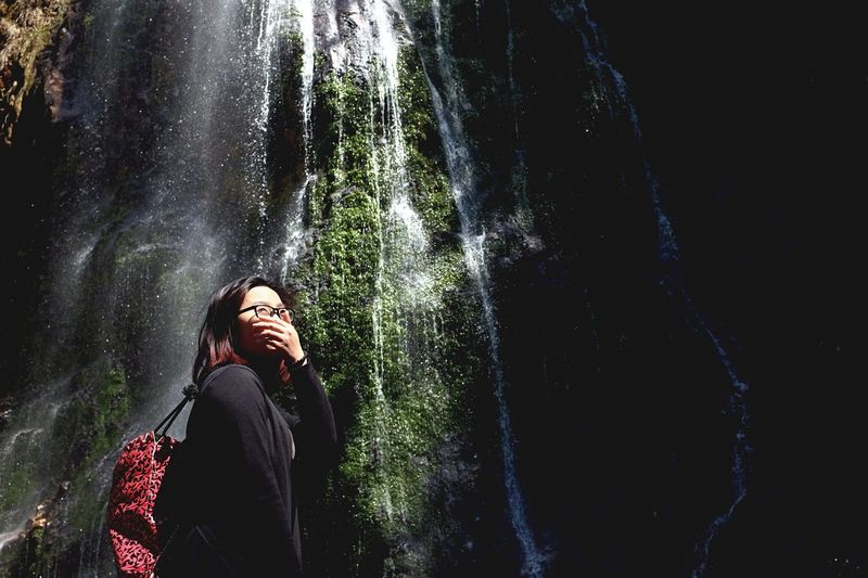 Low angle view of young woman against waterfall