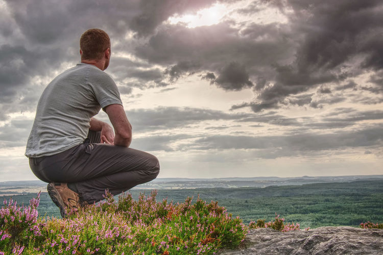 Man sitting on hill summit. conceptual scene. he wearing light outdoor clothes. he looking forward