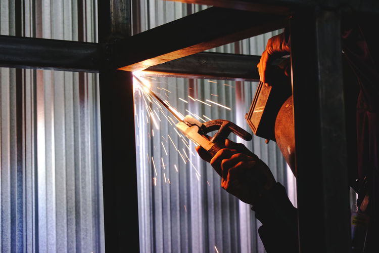 Man holding welding torch in factory