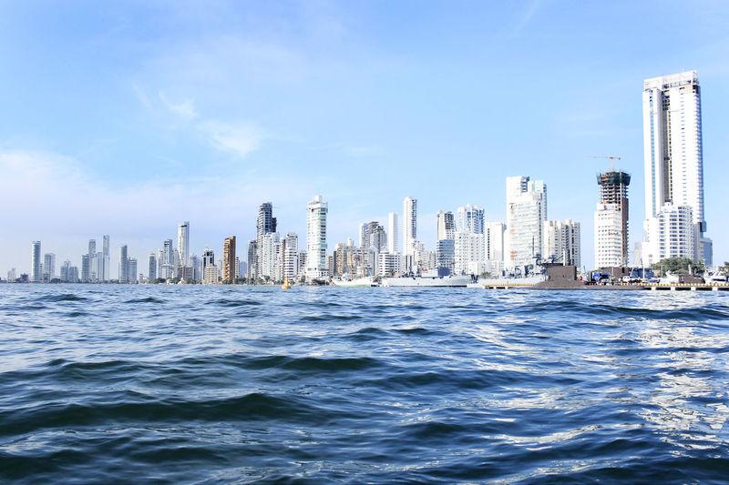 Sea and cityscape against blue sky