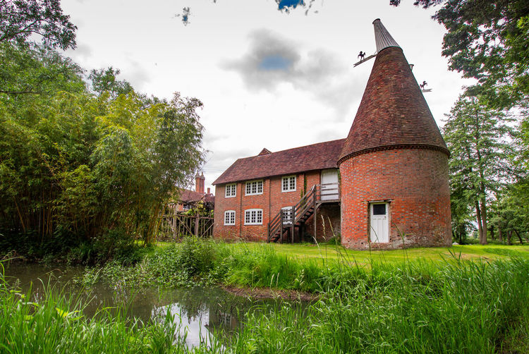 Oast House, Garden Of England, Kent, England Travel Destinations Tourism Hops Beer Brewing Drying Process Countryside Village Getty Images EyeEm Farm Vivid International Rural Scene Tranquil Scene Architecture Plant Tree No People Nature Day Sky Outdoors Built Structure Building Exterior Building Grass Cloud - Sky Green Color Water Growth House Land Field Canal