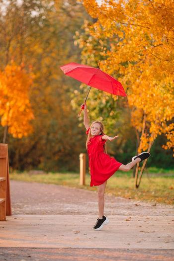 Woman holding umbrella during autumn