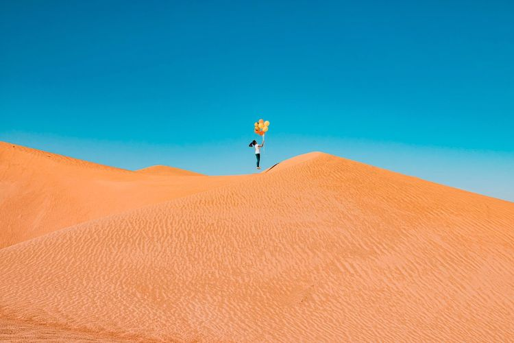 Sand Dune Arid Climate Desert Day Sand Blue Outdoors One Person Nature Clear Sky Low Angle View Tranquility Sky Scenics Real People Beauty In Nature People Liwa Desert UAE Abu Dhabi Lost In The Landscape Lost In The Landscape Connected By Travel Perspectives On Nature