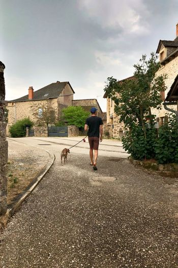 Man with dog walking in front of built structure