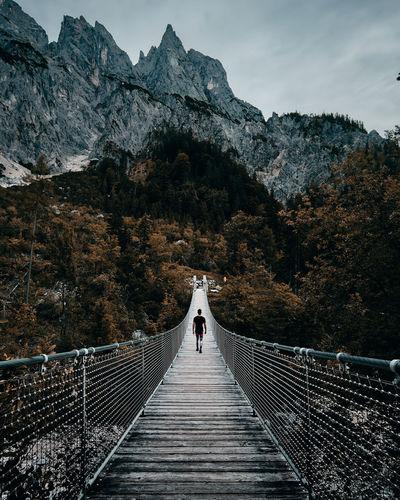 Rear view of man walking on footbridge leading towards mountain