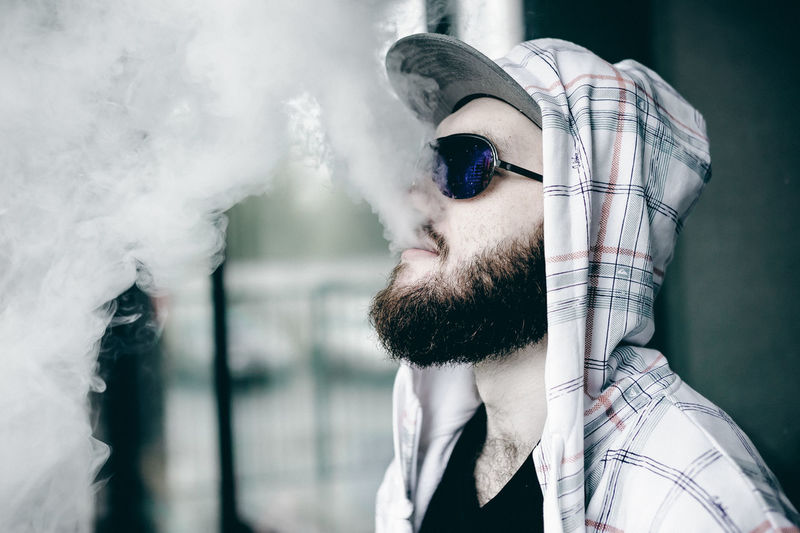 Vaping Bad Habit Beard Close-up Day Fashion Leisure Activity Lifestyles One Person Outdoors Real People Sunglasses Vape Young Adult Young Men