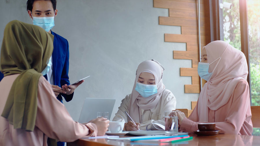 Businesspersons wearing mask having discussion in office