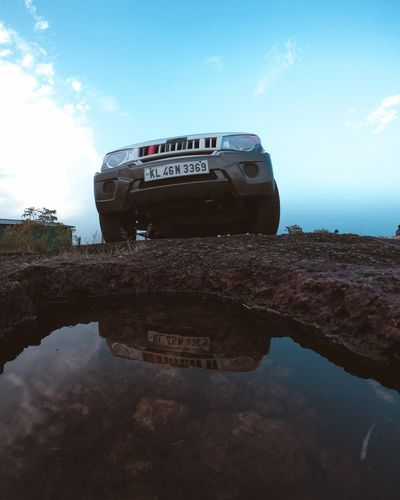Reflection of abandoned car on water against sky