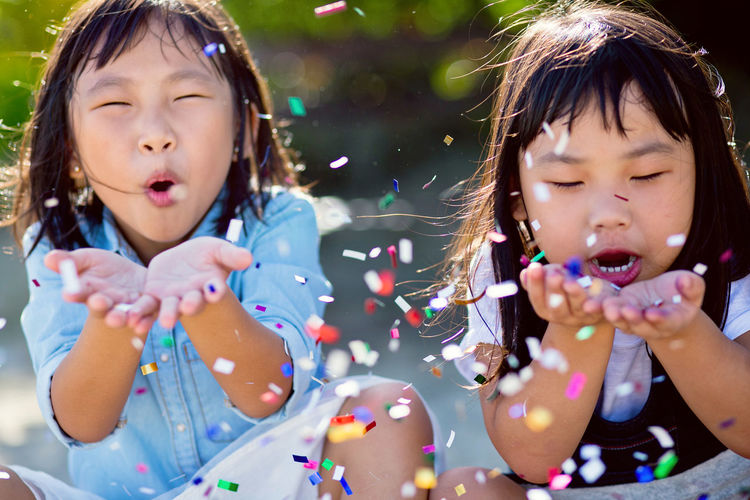 Close-Up Of Girls Blowing Confetti
