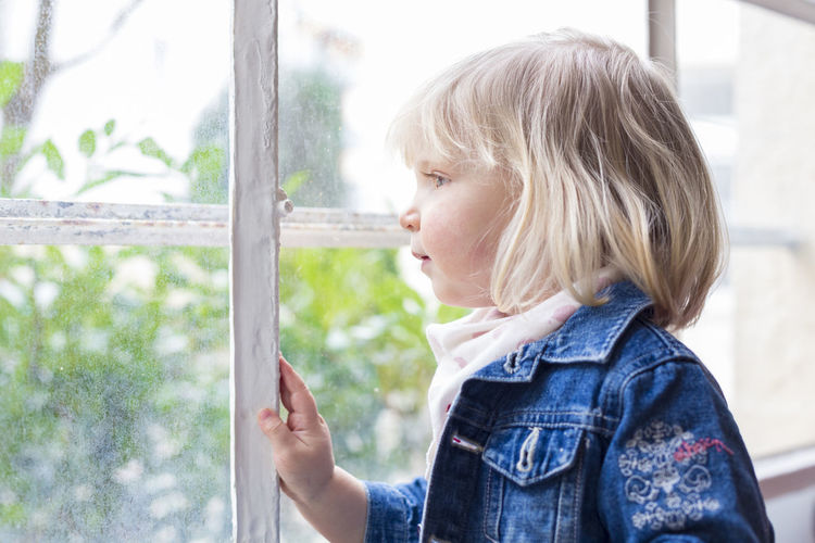 Side view of woman looking through window