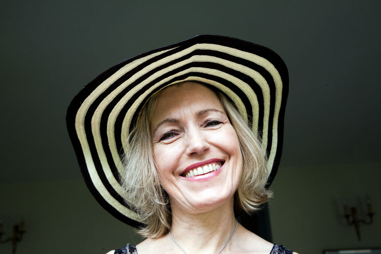 Portrait of smiling woman wearing hat at home