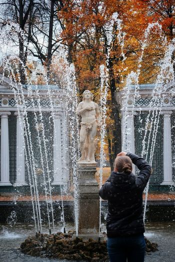 Rear view of man standing by fountain