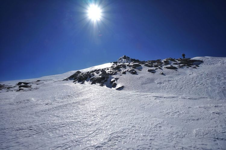 Snow covered mountain against sky on sunny day