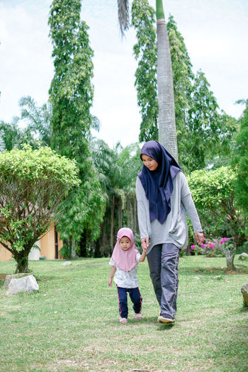 Rear view of mother and daughter standing against trees