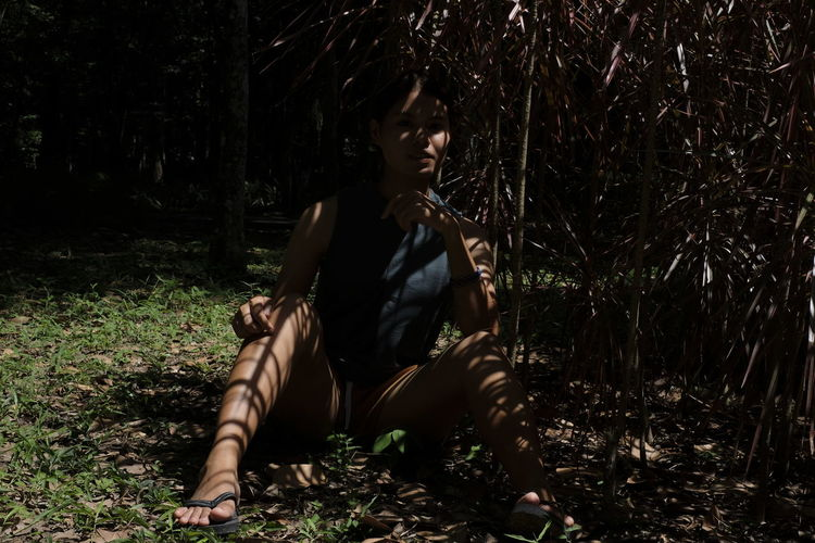 Thoughtful woman sitting under trees shadow in forest