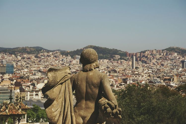 Naked Statue Overlooking Cityscape