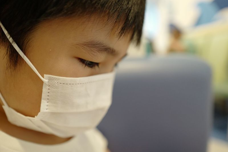 Close-up portrait of boy wearing surgical mask