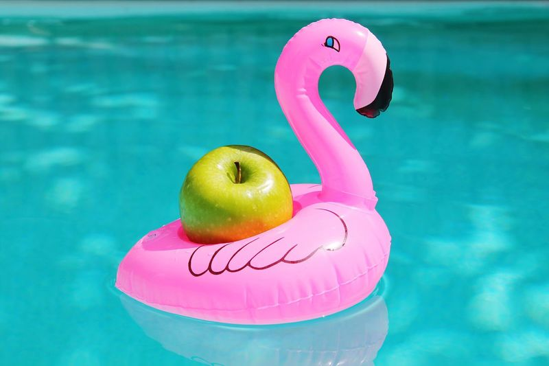 Close-Up Of Apple On Toy Flamingo In Swimming Pool