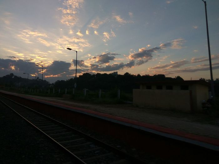 Railroad station against sky at sunset
