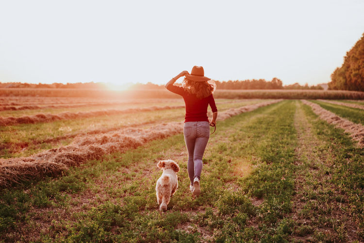 Rear view of woman running with dog on land