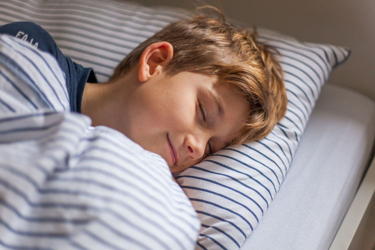 Portrait of boy sleeping in bed