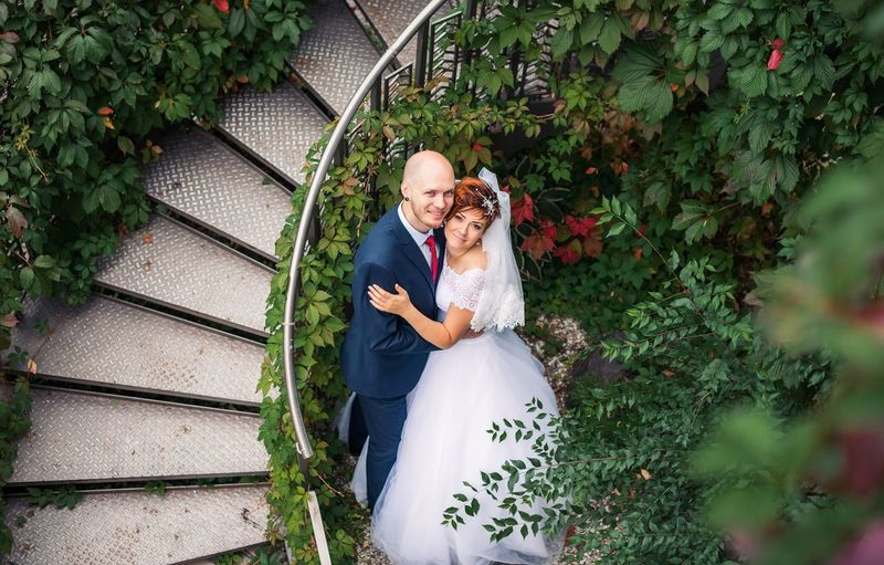 High Angle Portrait Of Bridal Couple Embracing By Staircase At Park