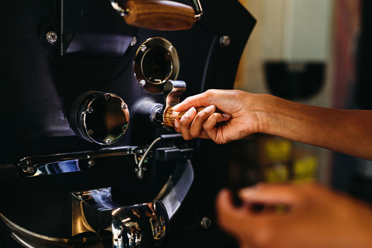 Cropped image of woman using coffee machine
