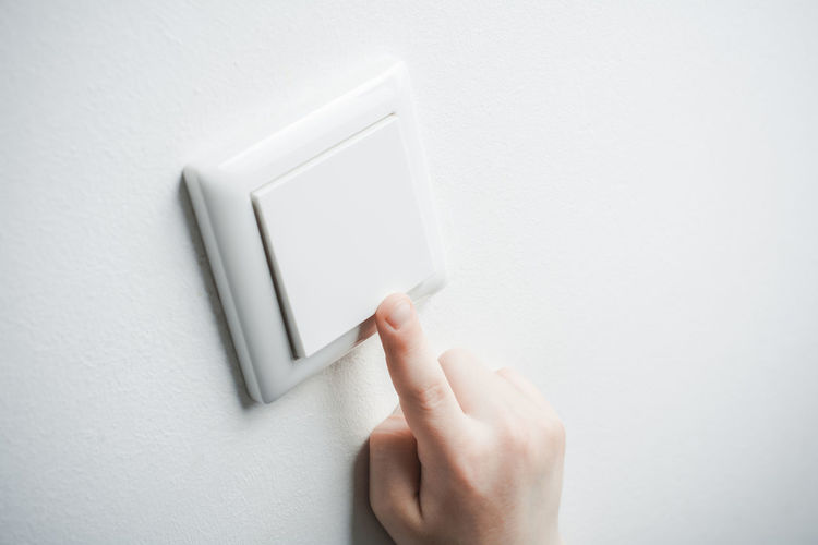 Close-up of human hand on white wall