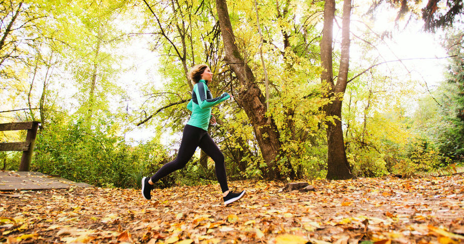 Adult Adults Only Autumn Day Exercising Forest Full Length Healthy Lifestyle Jogging Leaf Lifestyles Motion Nature One Person One Woman Only Only Women Outdoors Real People Running Sports Clothing Tree Vitality Women Young Adult Young Women