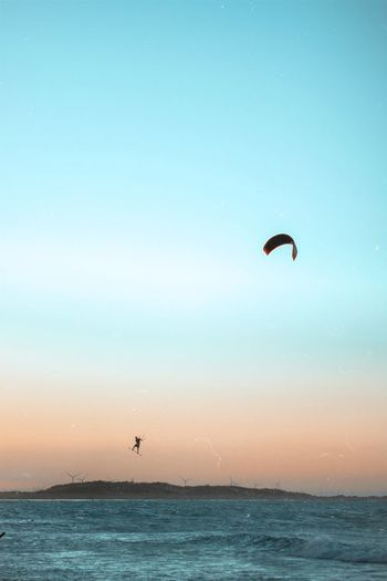 Person paragliding in sea against sky