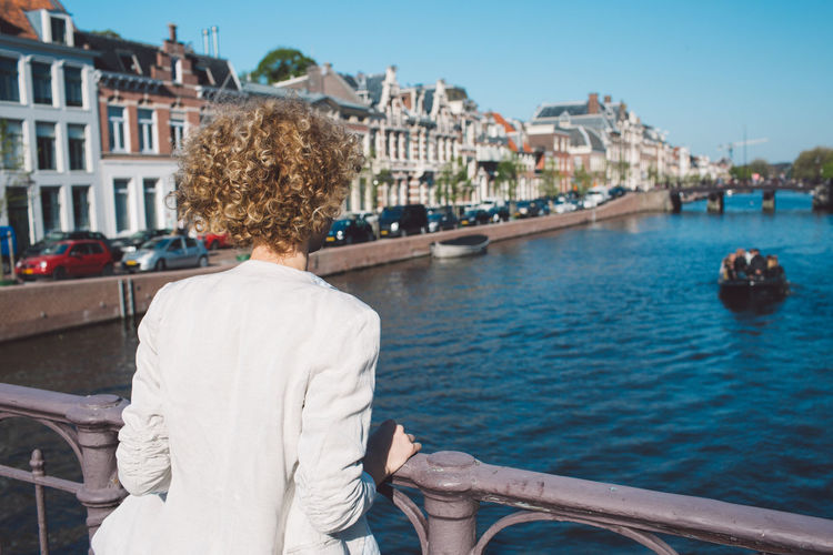 Rear view of woman standing by railing over canal in city