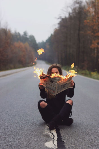 Young woman sitting on the empty road, holding burning paper in her hands