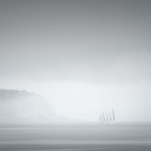 Boat Sailing In Sea Against Sky During Foggy Weather
