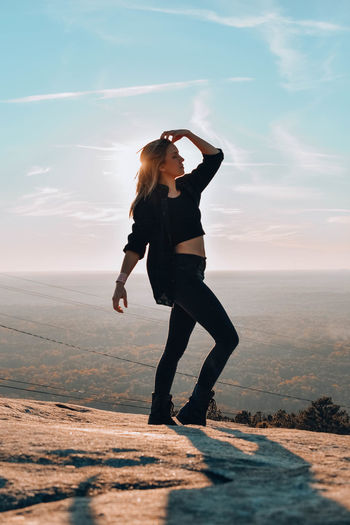 Full length of woman posing while standing on mountain against sky